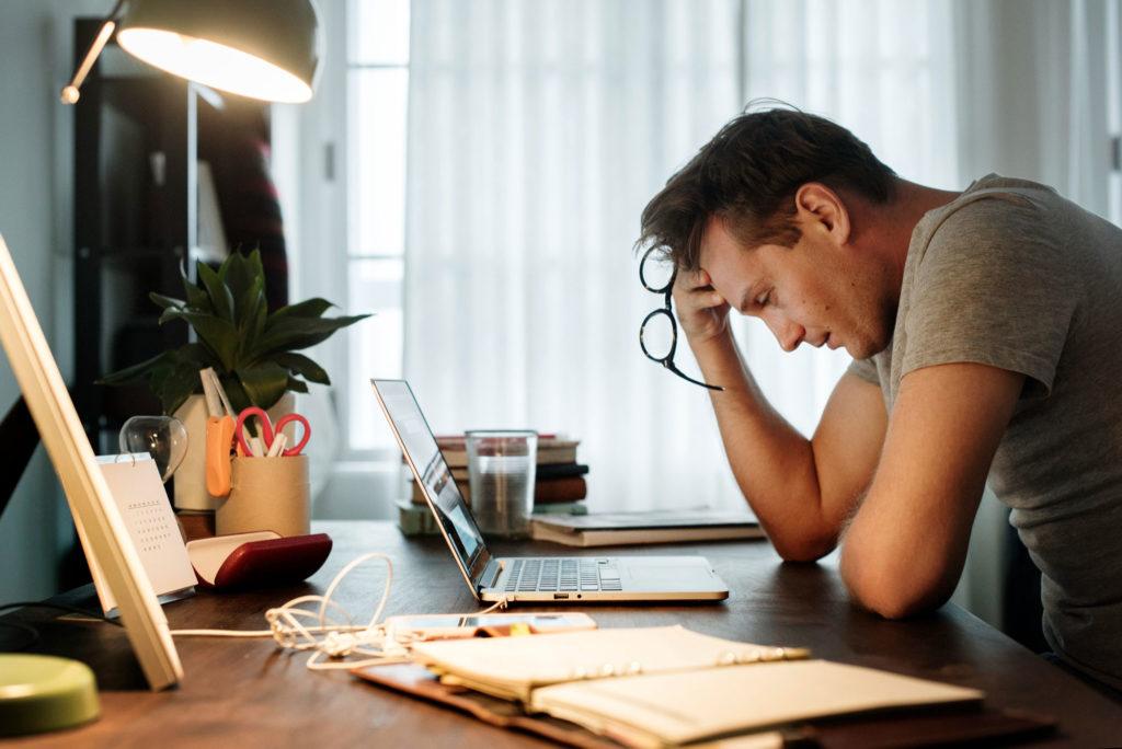 stressed man sitting at desk staring at computer screen