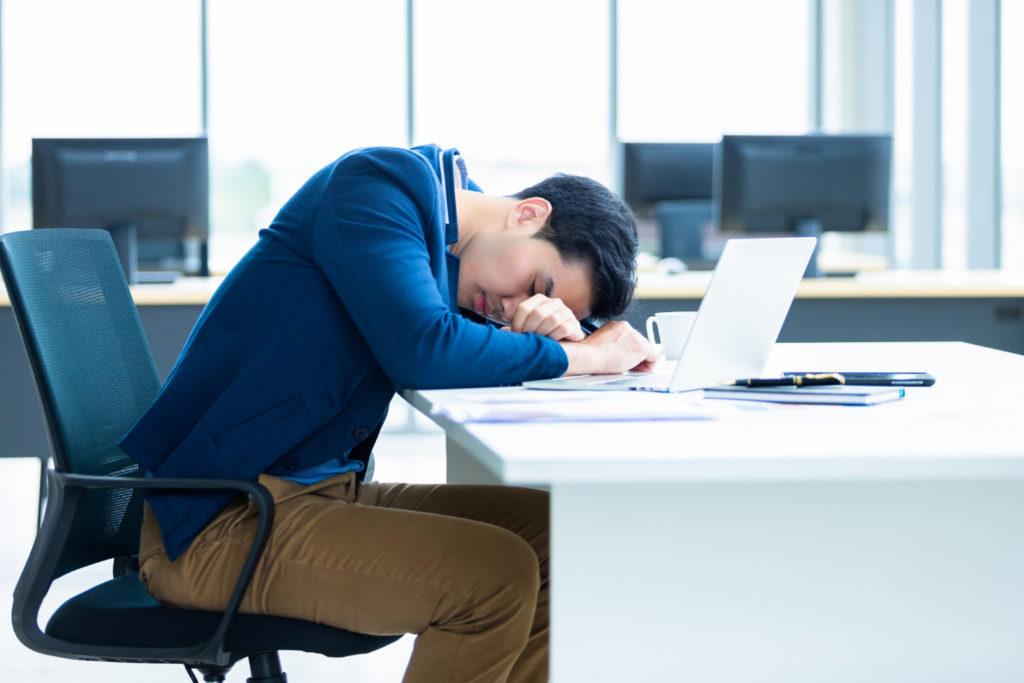 young man asleep on his computer desk