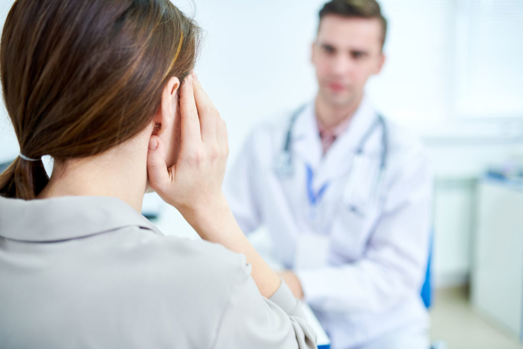 woman holding her ear and speaking with a doctor